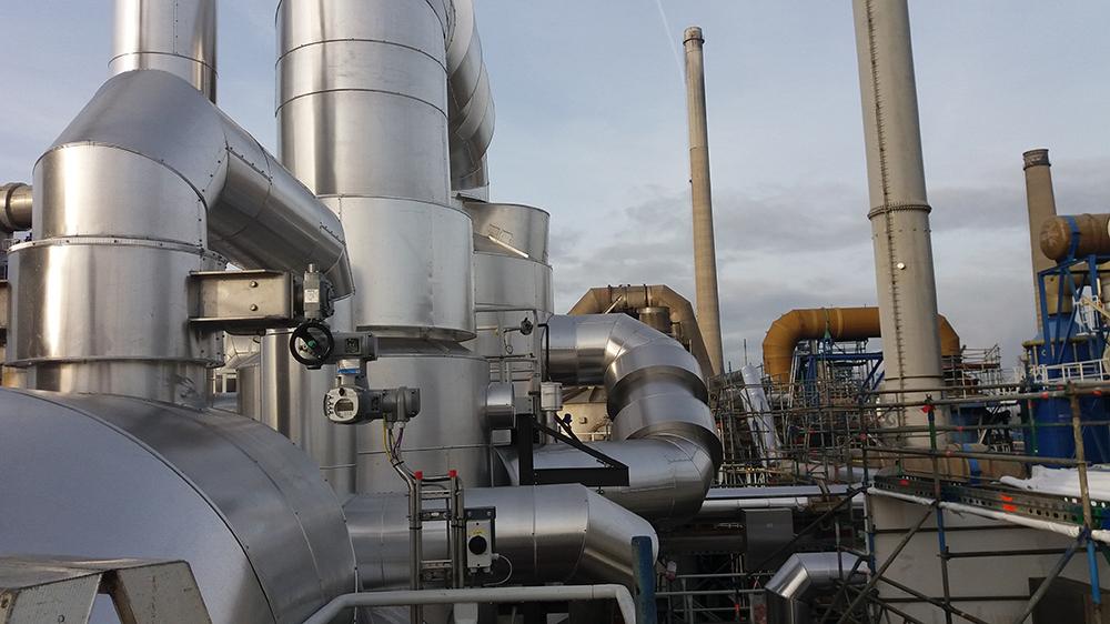 Montaż izolacji termicznej i akustycznej na instalacji rurociągów oraz kanałach spalin. Na załączonym zdjęciu widać nowo powstałą instalację, na zakładzie produkcyjnym w Belgii. Widoczny na zdjęciu kanał spalin z wykonaną izolacją grubości 200 milimetrów. Jako płaszcz ochronny izolacji użyto elementów wykonanych z blachy aluminiowej.